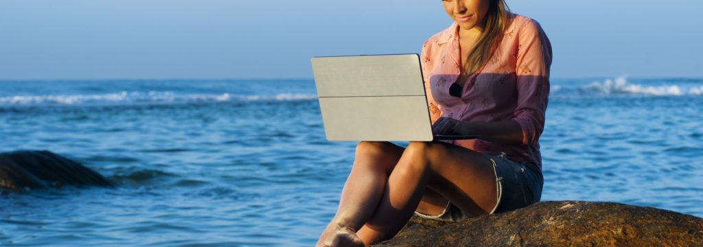 how to become a travel agent, woman with laptop on the beach